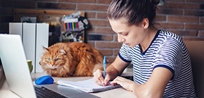 image of woman working at desk next to her cat