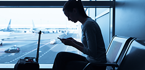 image of woman in airport looking at phone